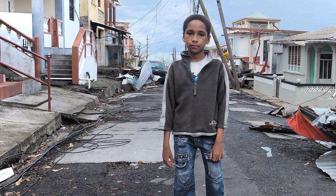 Young boy on a street in Puerto Rico damaged by hurricane Maria.